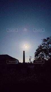 朝方の中秋の名月と煙突の写真・画像素材[4884377]