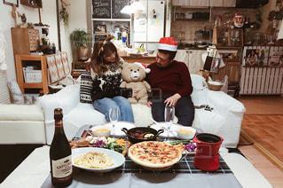 ピザのプレートをテーブルに座って人の写真・画像素材[941894]