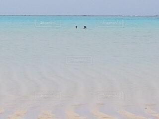 海の隣の砂浜の上に座っている青いフリスビーの写真・画像素材[4875298]