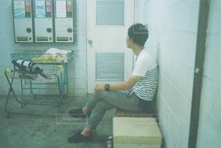 コインランドリーで待つ男の写真・画像素材[4888611]