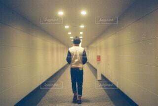 長い廊下を歩いている男性の写真・画像素材[4907250]