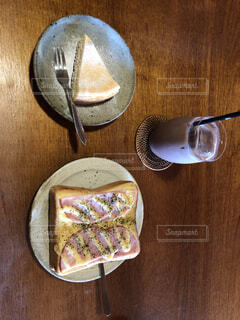 木製のテーブルの上に座っているケーキのスライスの写真・画像素材[4874537]