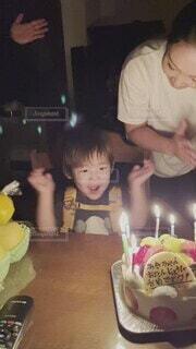 ママの誕生日ケーキのろうそくを主役のように消す男の子の写真・画像素材[4876704]