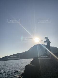 男性,自然,空,屋外,太陽,朝日,堤防,水面,釣り,リール,磯釣り,キャスティング,男の人,ジギング,ショアジギング