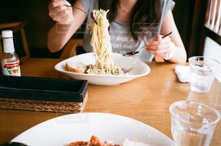 食事のテーブルに座っている女性の写真・画像素材[1678714]