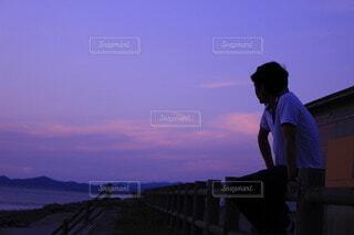 夕方海を見つめる男性の写真・画像素材[4916839]