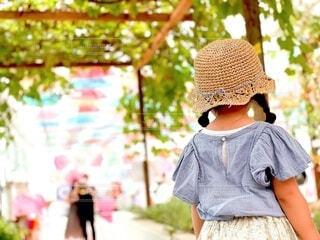 子ども,夏,屋外,緑,植物,後ろ姿,帽子,女の子,少女,トンネル,3歳,おさげ,小さい子