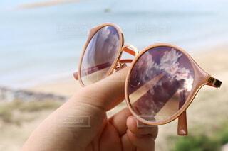 海でサングラスを持つ手の写真・画像素材[4915027]
