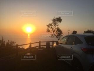 水平線へ沈む夕陽に照らされる車の写真・画像素材[4928778]