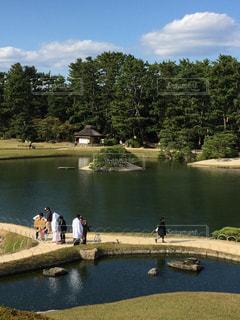水の体の横に立っている人のグループの写真・画像素材[1021399]