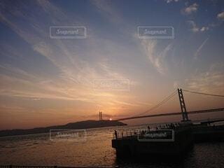 夕陽と大橋と釣り人の写真・画像素材[4941528]
