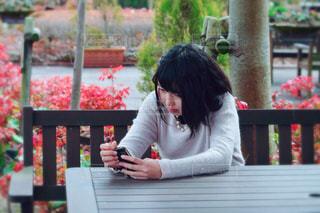 スマートフォンを使用してテーブルに座っている人の写真・画像素材[1059251]