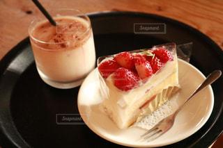 コーヒーカップの横にある皿の上のケーキの写真・画像素材[1883144]