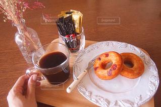 一杯のコーヒーとドーナツの木製テーブルの上に座っています。の写真・画像素材[1295385]
