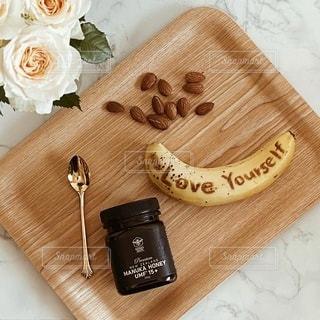 木のまな板の上に座っているバナナの写真・画像素材[3366501]