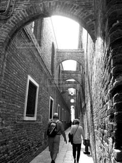 れんが造りの建物の前の歩道を歩いている人 - No.813677