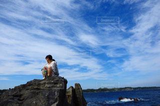 水の体の横にある岩の上に座っている男の写真・画像素材[786013]