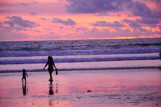 背景の夕日とビーチの上を歩く人々 のグループの写真・画像素材[786242]