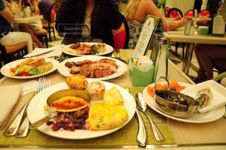 食品のプレートをテーブルに座っている人々 のグループ - No.823652