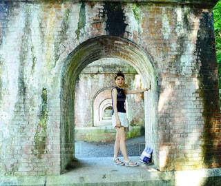 石造りの建物の前に立っている人の写真・画像素材[906165]