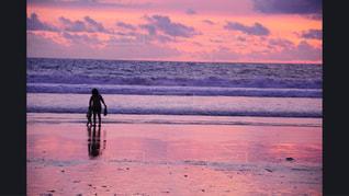 背景の夕日とビーチの上を歩く人々 のグループ - No.981198