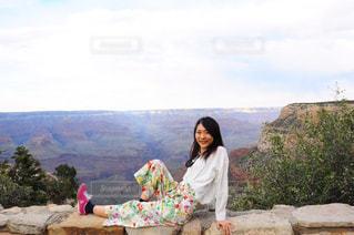 岩の上に座っている人の写真・画像素材[1025298]