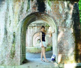 石造りの建物の前に立っている人 - No.1026206