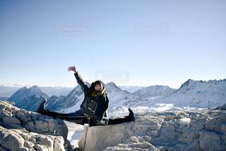 雪に覆われた山の頂上に立っている男の写真・画像素材[1615831]