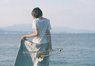水の体の横に立っている人の写真・画像素材[732423]