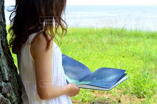 若い女の子は草の中に座っています。の写真・画像素材[737238]