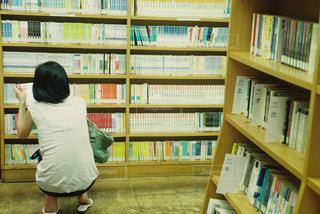 本の棚の前で座っている女の子 - No.750917