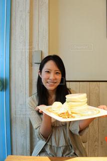 食事のテーブルに座っている女性の写真・画像素材[751818]