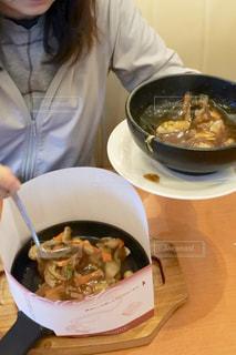 食品のボウルで、テーブルに座っている女性の写真・画像素材[781212]