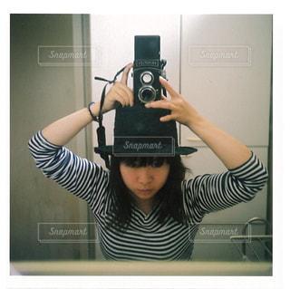 カメラにポーズ鏡の前に立っている女性の写真・画像素材[781443]