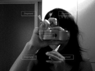 カメラにポーズを鏡の前で彼女の歯を磨く女性の写真・画像素材[781454]