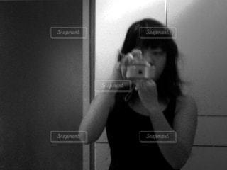 カメラにポーズを鏡の前で彼女の歯を磨く女性の写真・画像素材[781455]