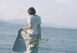 水の体の横に立っている人の写真・画像素材[808029]