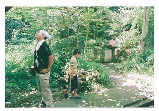 木の隣に立っている男の写真・画像素材[823286]