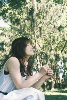 木の隣に立っている女性の写真・画像素材[856781]