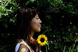 黄色い花を持っている人の写真・画像素材[888528]