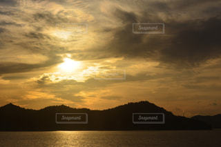 背景の山が付いている水の体に沈む夕日の写真・画像素材[915945]