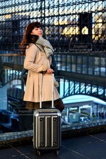 荷物の袋の横に立っている女性 - No.916215