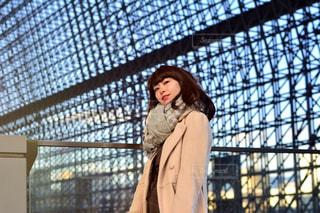 フェンスの前に立っている女性の写真・画像素材[916218]