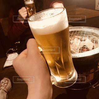 テーブルの上のビールのガラスを保持している人 - No.942732