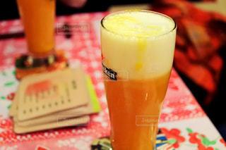 コーヒー カップの横にあるオレンジ ジュースのガラスの写真・画像素材[942751]