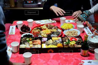食物と一緒にテーブルに座っている女性の写真・画像素材[954913]