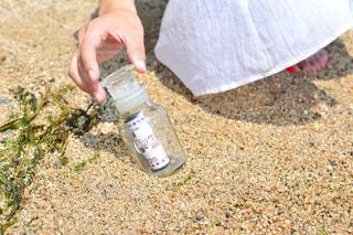 砂浜でフリスビーを持っている手 - No.969521