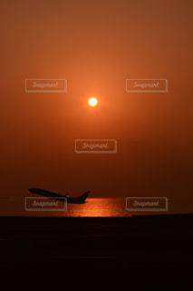 夕日で空を飛んでいる飛行機の写真・画像素材[984494]