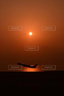 夕日で空を飛んでいる飛行機 - No.984495