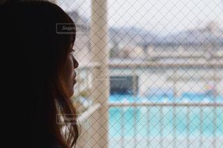 ウィンドウの前に立っている女性の写真・画像素材[995249]